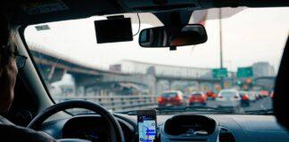 Wnętrze auta z kierowcą korzystającym z nawigacji na telefonie.