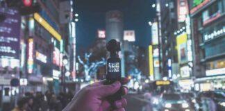 Anonimowa osoba nagrywa przechodniów w oświetlonym, tętniącym życiem, mieście. Stanowi to przetwarzanie danych osobowych w postaci wizerunków.