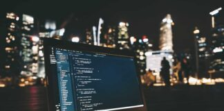 laptop z kodem programu na ekranie na tle rozświetlonego miasta nocą