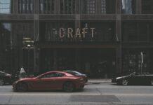 """Ulica miasta, po której przejeżdżają samochody, w tle budynek, na którym umieszczony jest neon z napisem """"CRAFT"""""""