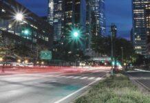 Zielone światło na pustej droga w mieście pomiędzy wieżowcami.
