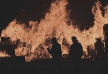 Ludzie na tle płomieni w nocy