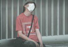 Zmęczony Człowiek w masce ochronnej siedzi na ławce